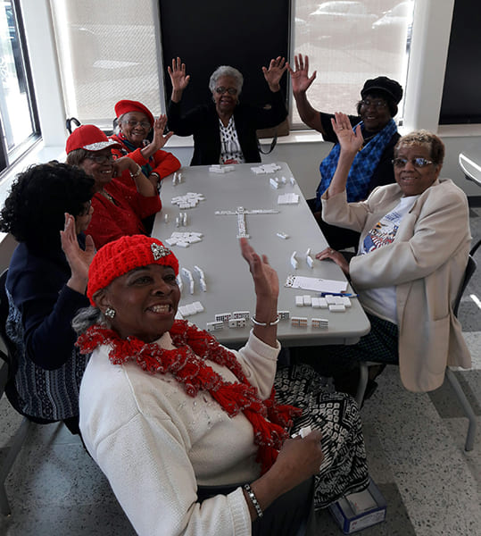 Seven Rose Centers participants sitting at a table playing dominoes while smiling and waving