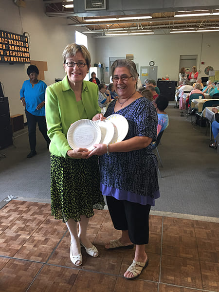 Two Rose Centers participants holding up paper plates explaining why Rose Center meals matter to them for the hashtag SaveLunch campaign