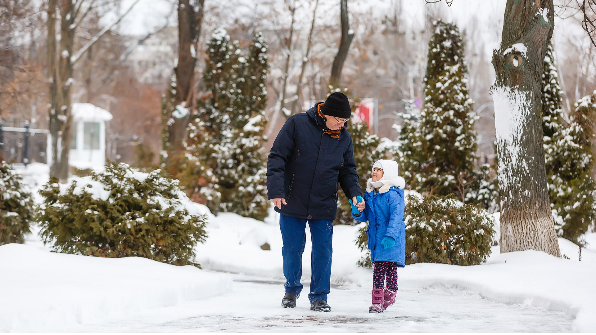 Home-Page-Older-Adult-walking-down-snowy-street-with-grandchild