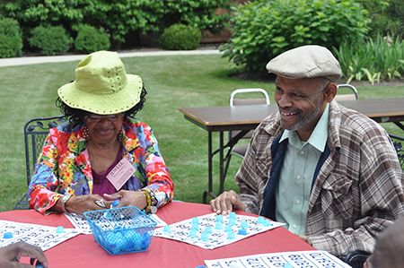Adult Day Program participants sitting at a round table playing bingo outdoors