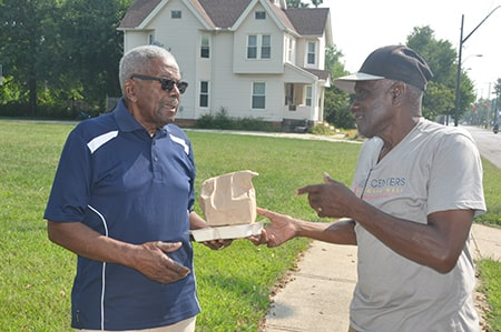 Rose Centers for Aging Well Home-Delivered Meals driver/jumper handing home-delivered meal participant their lunch