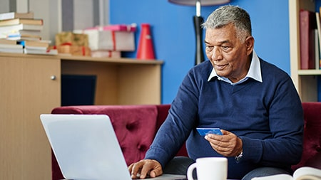 Man sitting at laptop computer holding a credit card.